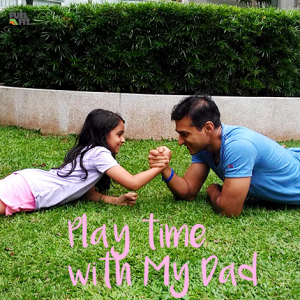 Child and Dad arm wrestle for fun on grass